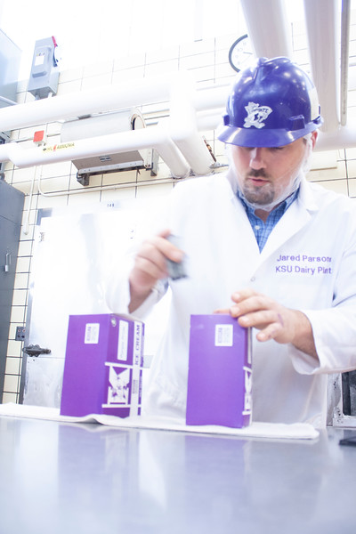 Jared Parsons, dairy plant manager, stamps freshly filled containers of purple pride ice cream at Call Hall's dairy plant on Tuesday, April 24, 2018. (Tiffany Roney | Collegian Media Group)