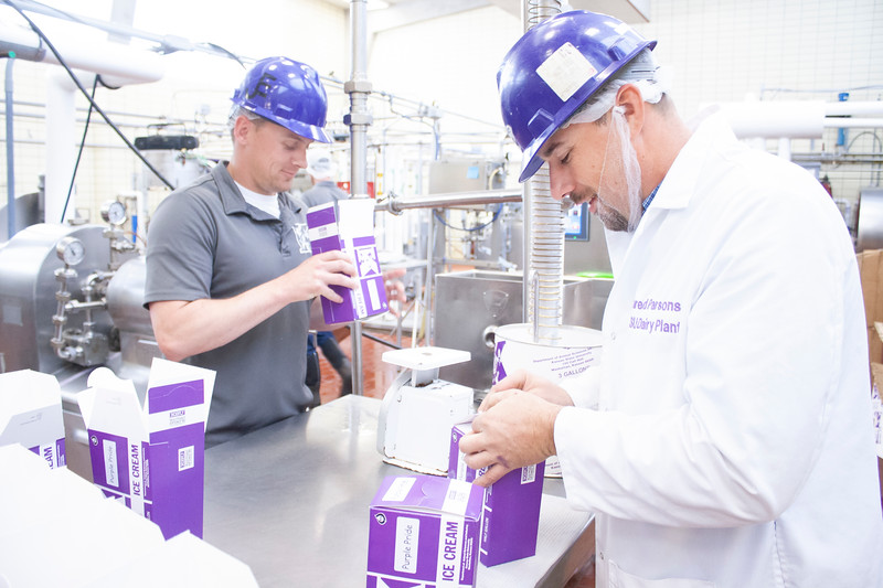 Jared Parsons (right), dairy plant manager, closes the lid of a half-gallon of freshly churned purple pride ice cream while Jake Eckert, agricultural technician senior, fills another gallon with the blueberry-laced treat at Call Hall's dairy plant on Tuesday, April 24, 2018. (Tiffany Roney | Collegian Media Group)