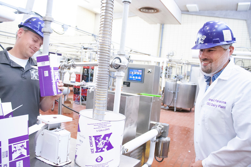 Jake Eckert (left), agricultural technician senior, and Jared Parsons, dairy plant manager, fill containers with fresh purple pride ice cream at Call Hall's dairy plant, on Tuesday, April 24, 2018. (Tiffany Roney | Collegian Media Group)
