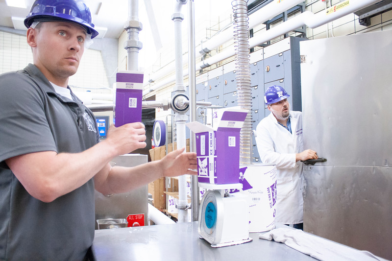 Jake Eckert, agricultural technician senior, fills one container with purple pride ice cream while weighing another freshly filled container to ensure proper air content. Behind him, Jared Parsons, dairy plant manager, talks to another employee from the door of the walk-in freezer, where half-gallon containers of ice cream set for at least one day before going forth from the plant. The team churned vanilla, cookie dough, peach, purple pride and strawberry ice cream at Call on Tuesday, April 24, 2018. (Tiffany Roney | Collegian Media Group)