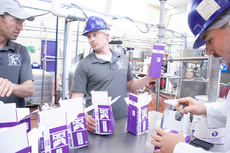 Jake Eckert (center), agricultural technician senior, holds a container as it fills with purple pride ice cream while communicating with Tony Sauvage (left), agricultural technician senior, and Jared Parsons, dairy plant manager at Call Hall's dairy plant, on Tuesday, April 24, 2018. (Tiffany Roney | Collegian Media Group)