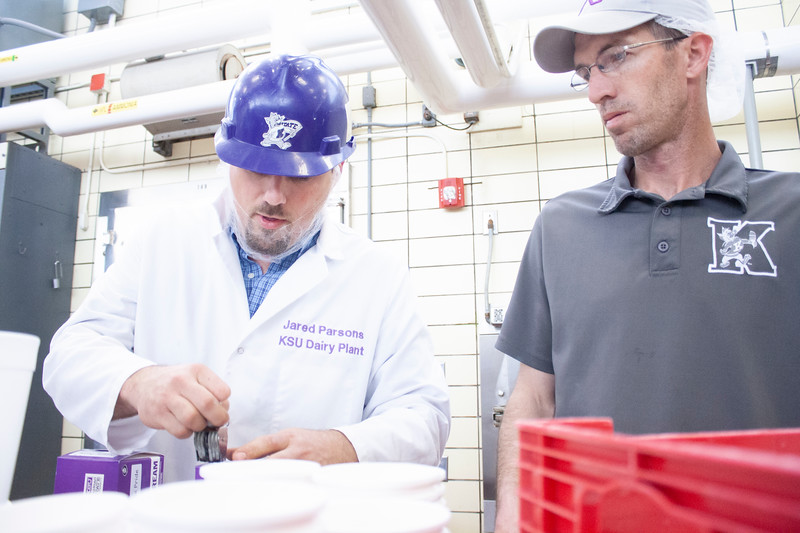 Jared Parsons, dairy plant manager, stamps containers of purple pride ice cream while Tony Sauvage (right), agricultural technician senior, stands ready to stack the next set of containers at Call Hall's dairy plant, on Tuesday, April 24, 2018. (Tiffany Roney | Collegian Media Group)