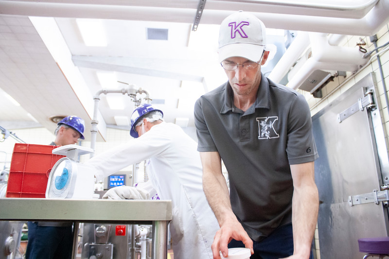 Tony Sauvage, agricultural technician senior, stacks to-go containers of purple pride ice cream in Call Hall's dairy plant, on Tuesday, April 24, 2018. Behind him, Jake Eckert (left), also an agricultural technician senior, and Jared Parsons, dairy plant manager, fill and weigh the containers with fresh ice cream. (Tiffany Roney | Collegian Media Group)
