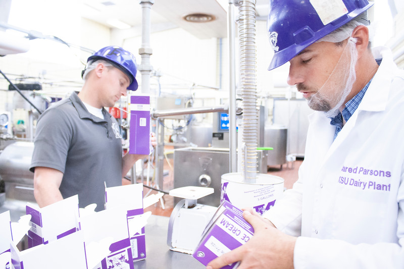 Jared Parsons (front), dairy plant manager, works with filled containers of ice cream while Jake Eckert (background), agricultural technician senior, holds fills another container with purple pride ice cream at Call Hall's dairy plant, on Tuesday, April 24, 2018. (Tiffany Roney | Collegian Media Group)