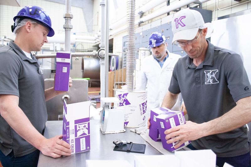 Jake Eckert (from left), agricultural technician senior; Jared Parsons, dairy plant manager; and Tony Sauvage, agricultural technician senior, fill, stamp and stack containers of fresh purple pride ice cream at Call Hall's dairy plant, on Tuesday, April 24, 2018. (Tiffany Roney | Collegian Media Group)
