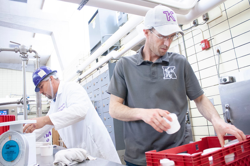 Tony Sauvage, agricultural technician senior, stacks to-go containers of purple pride ice cream and Jared Parsons (back-left), dairy plant manager, prepares the ice cream at Call Hall's dairy plant, on Tuesday, April 24, 2018. (Tiffany Roney | Collegian Media Group)