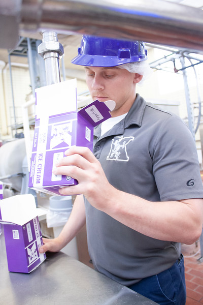 Jake Eckert, agricultural technician senior, eyes a half-gallon of purple pride ice cream as he helps prepare hundreds of gallons of the blueberry-laced treat at Call Hall's dairy plant on Tuesday, April 24, 2018. (Tiffany Roney | Collegian Media Group)