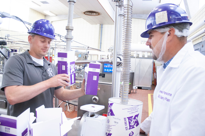 Jake Eckert, agricultural technician senior, uses one hand to fill a half-gallon container with purple pride ice cream while preparing to fill the next container. Meanwhile, Jared Parsons, dairy plant manager, oversees the filling of a three-gallon container with him and waits to stamp the next half-gallon container at Call Hall's dairy plant, on Tuesday, April 24, 2018. (Tiffany Roney | Collegian Media Group)