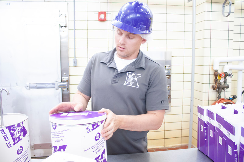 Jake Eckert, agricultural technician senior, places the lid on a freshly filled three-gallon container of purple pride ice cream Call Hall's dairy plant on Tuesday, April 24, 2018. (Tiffany Roney | Collegian Media Group)
