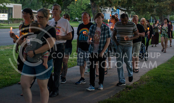 Members of the Manhattan LGBT community, along with allies, carried candles as they walked down the sidewalk on Poyntz following the candlelight vigil on June 12, 2016. The vigil was arranged the day of the mass shooting. (George Walker | The Collegian)