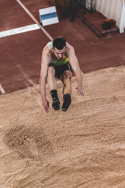 Arms and legs extended, K-State junior Aaron Booth prepares to land while taking part in the long jump during the Carol Robinson/Attila Zsivoczky Pentathlon in Ahern on December 7, 2018. (Alex Todd   Collegian Media Group)