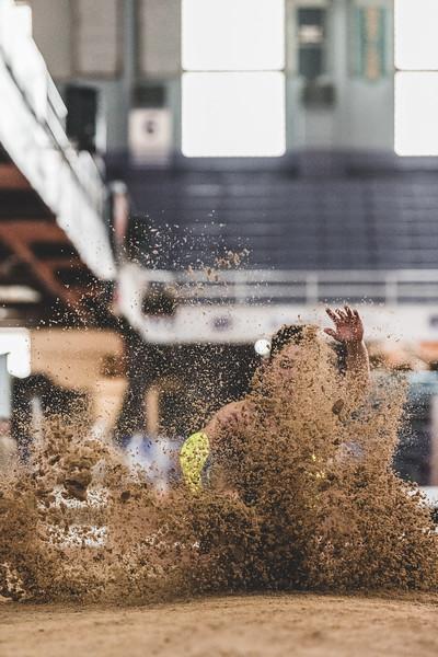 Sand flies everywhere as K-State senior Morgan Coffman finishes her long jump during the Carol Robinson/Attila Zsivoczky Pentathlon in Ahern on December 7, 2018. (Alex Todd   Collegian Media Group)