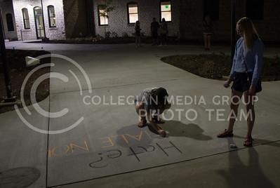 "Lucie Rogers, junior in civil engineering, and Kathryn Brown, junior in computer science, write ""Hate? HALE NO!"" in chalk outside of Hale Library on September 14, 2017.  (Regan Tokos | Collegian Media Group)"