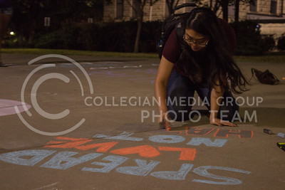 """Savannah Rattanavong, senior in journalism, writes """"spread love not hate"""" in chalk outside the lower exit of Hale Library on September 13, 2017. The chalking was in response to white nationalist posters found on campus earlier that day. (Regan Tokos 