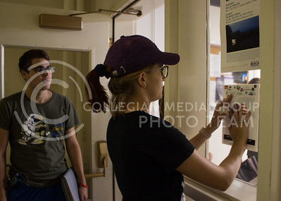 Madeline Ames, sophomore in political science, hangs a poster sponsored by multiple student organizations on a window in Willard Hall on September 13, 2017. The posters were made in unison with multiple organizations to promote peace after white nationalist posters were found on campus. (Regan Tokos | Collegian Media Group)