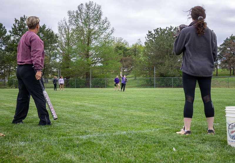 Kayla Mesh (right), the K-State club softball team's president, helps head coach Connie Miller hit fly balls and grounders to team members at a Monday night practice.  The girls wrapped up the Spring portion of their season last weekend at the Mid-American Regional Tournament in Kansas City.  (Caleb Pfeifer | Collegian Media Group)