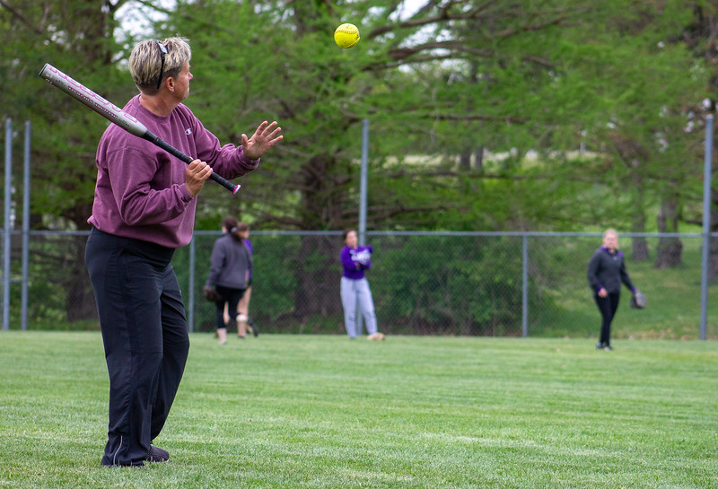 Connie Miller, the K-State club softball team's head coach, hits fly balls and grounders to team members at a Monday night practice.  The girls wrapped up the Spring portion of their season last weekend at the Mid-American Regional Tournament in Kansas City.  (Caleb Pfeifer | Collegian Media Group)