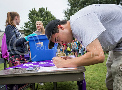 Greg Woods, senior in journalism, signs up for the Bakery Club during the College of Agriculture Annual Watermelon Feed on Aug. 30, 2016. (John Benfer | The Collegian)