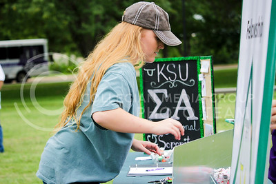Nataliy Timmons, junior in animal science, sets up the Sigma Alpha table to recruit girls to the Sigma Alpha sorority as they pass by the agriculture organizations at the College of Agriculture Annual Watermelon Feed on Aug. 30, 2016, at Weber Arena. The annual watermelon feed was set up by the college to get students involved in the agriculture department and organizations. (Alanud Alanazi | The Collegian)