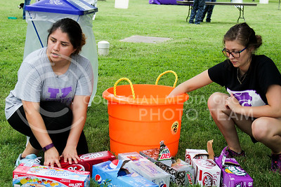 """Tiffany Medina, junior in animal science, and Catie Meeth, junior in animal science and business, places drinks in a bucket full of ice, ready to serve to students as they browse the agriculture organizations during the College of Agriculture Annual Watermelon Feed on Aug. 30, 2016, at Weber Arena. """"[The watermelon feed] is an organization to get more people invloved with agriculture and it's also really good for incoming freshmen to find clubs that they're interested in,"""" Meeth said. (Alanud Alanazi 