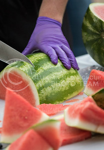 A worker slices a watermelon at the College of Agriculture Annual Watermelon Feed on Aug. 30, 2016. (John Benfer | The Collegian)