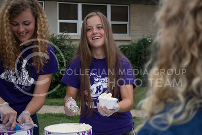 Brianna Yates (right), junior in animal sciences and industry, and Stephanie Geven, junior in animal sciences and industry, serve ice cream to students and guests during the College of Agriculture Annual Watermelon Feed on the Weber Hall lawn on Aug. 30, 2016. (Miranda Snyder | The Collegian)