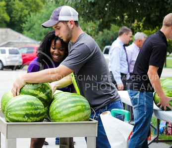 Shakyra Evertt, senior in agriculture education, and Bret Gum, junior in agriculture ecnomics, lift watermelon from the cart to place on the serving table to begin cutting them and serving them to students as they browse the agriculture organizations during the College of Agriculture Annual Watermelon Feed on Aug. 30, 2016, at Weber Arena. (Alanud Alanazi | The Collegian)