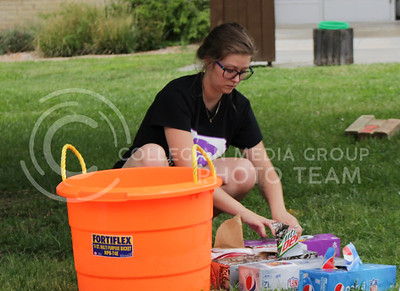 """Catie Meeth, junior in animal science and business, places soda in a bucket full of ice, ready to serve to students as they browse the agriculture organizations during the College of Agriculture Annual Watermelon Feed on Aug. 30, 2016, at Weber Arena. """"[The watermelon feed] is an organization to get more people invloved with agriculture and it's also really good for incoming freshmen to find clubs that they're interested in,"""" Meeth said. (Alanud Alanazi 