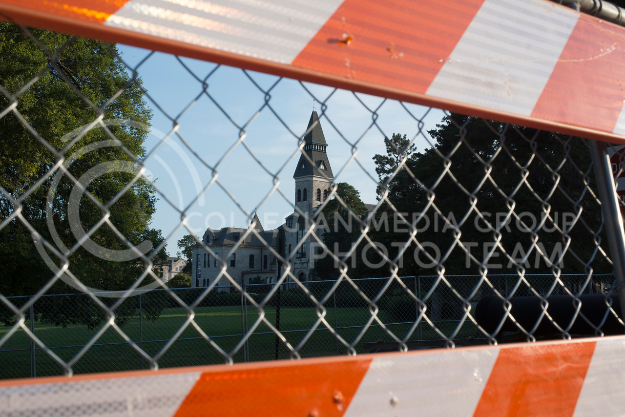 Anderson Hall peaks through fences and road signs as construction continues on Mid-Campus Drive as well as other locations around campus on July 5, 2016. (Evert Nelson | The Collegian)