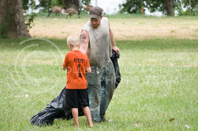 A father and son spent the morning after the Country Stampede cleaning up the campgrounds of Tuttle Creek Park, where the festival was hosted from June 21 - 23. (Alex Masson | Collegian Media Group)