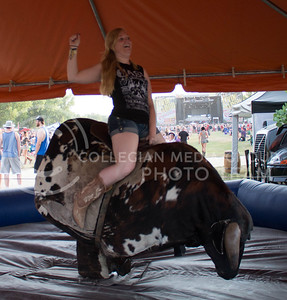 Alexis Ford, junior in nursing, smiles to her friends as she rides the mechanical bull during Day 1 of Country Stampede on Thursday. (Photo by Michael Weninger | The Collegian)
