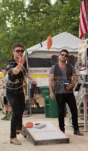 Guitarist for Cassadee Pope, Darrek Bahr, plays Cornhole Toss with his bandmates after finishing up on stage during day 1 of Country Stampede on Thursday. (Photo by Michael Weninger | The Collegian)