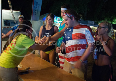 Abigail Stedry, senior in animal science at KSU, helps patrons put on their wristbands at the drinks table during day 1 of Country Stampede on Thursday. (Photo by Michael Weninger | The Collegian)
