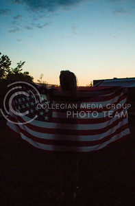 Christine Morris of Blair, Nebraska, watches the sunset over the Stampede campgrounds on Friday evening. (Photo by Michael Weninger | The Collegian)