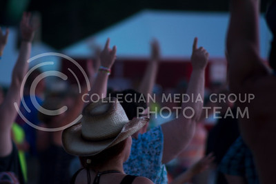Fans in the crowd raise their arms in hopes of catching a free gift from the staff on stage at Country Stampede on July 24th, 2016. (Sarah Falcon | The Collegian)