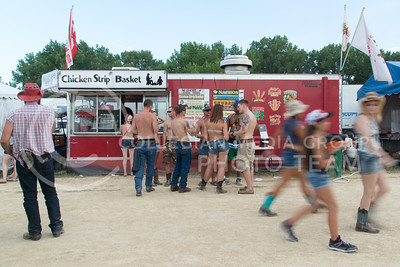 People walk past a Kolanders Concession stand selling a variety of food at Country Stampede on June 25, 2016. (Photo by Evert Nelson | The Collegian)