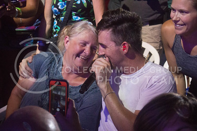 Jake Owen sits and sings next to a concertgoer during his performance Saturday night at Country Stampede. (Photo by Michael Weninger | The Collegian)
