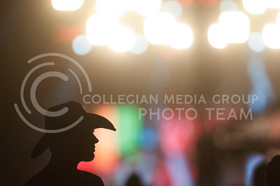 A man and his cowboy hat are sihouetted against the bright stage while Jake Owen performs at Country Stampede on June 25, 2016. (Photo by Evert Nelson | The Collegian)
