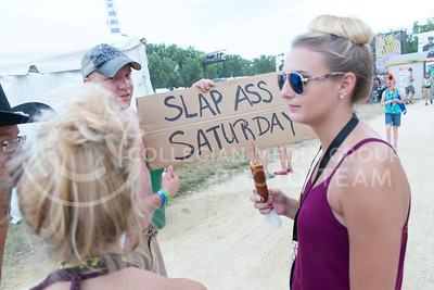 Guys hold a sign hoping to entice women passing through the Country Stampede site on June 25, 2016. (Photo by Evert Nelson | The Collegian)