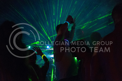 A partygoer throws his hands in the air as lasers illuminated by fog take over the campsite outside of Country Stampede at Tuttle Creek State Park on June 25 , 2016. (Photo by Evert Nelson |The Collegian)