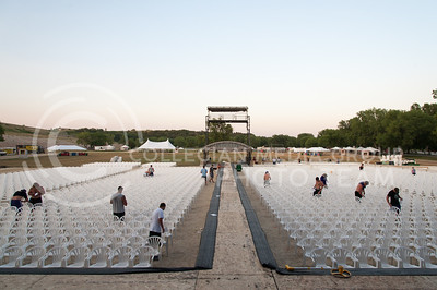 Staff for Country Stampede work to tie down hundreds of lawn chairs in front of the main stage on June 21, 2016. (Photo by Evert Nelson | The Collegian)