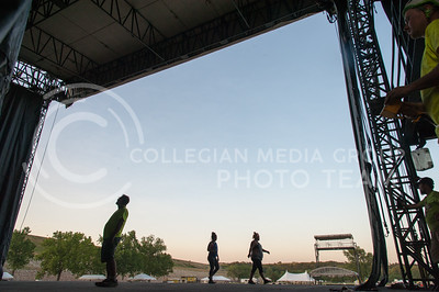 Crew members for Premiere Global Productions look up at the main stage of Country Stampede watching other crews as they secure the roof fixtures on June 21, 2016 at Tuttle Creek State Park. (Photo by Evert Nelson | The Collegian)