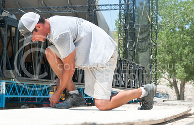 Zach Serigny, from Louisiana, works to screw down wooden boards to stage extensions on June 21, 2016 in preparations for Country Stampede. (Photo by Evert Nelson | The Collegian)