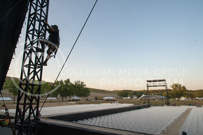 John Garcia, with Premiere Global Productions, climbs up a post on the main stage to tighten down the roof during setup for Country Stampede on June 21, 2016 at Tuttle Creek State Park. (Photo by Evert Nelson |The Collegian)