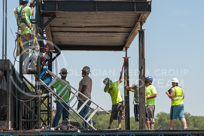 Crews for Premiere Global Productions work to erect the right side of the main stage of Country Stampede on June 21, 2016 at Tuttle Creek State Park. (Photo by Evert Nelson | The Collegian)