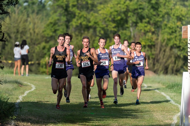 The K-State men's cross country team following two Wichita State runners during the J.K. Gold Classic in Augusta, KS on September 1, 2018. (Alex Todd | Collegian Media Group)