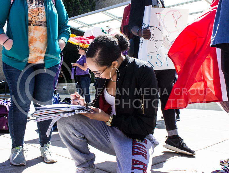 Sarah Mullin, freshman in psychology, kneels down to sign a petition to keep Deferred Action for Childhood Arrival (DACA) at a rally in solidarity with DACA recipients held in Bosco Plaza on September 6, 2017. (Regan Tokos | Collegian Media Group)