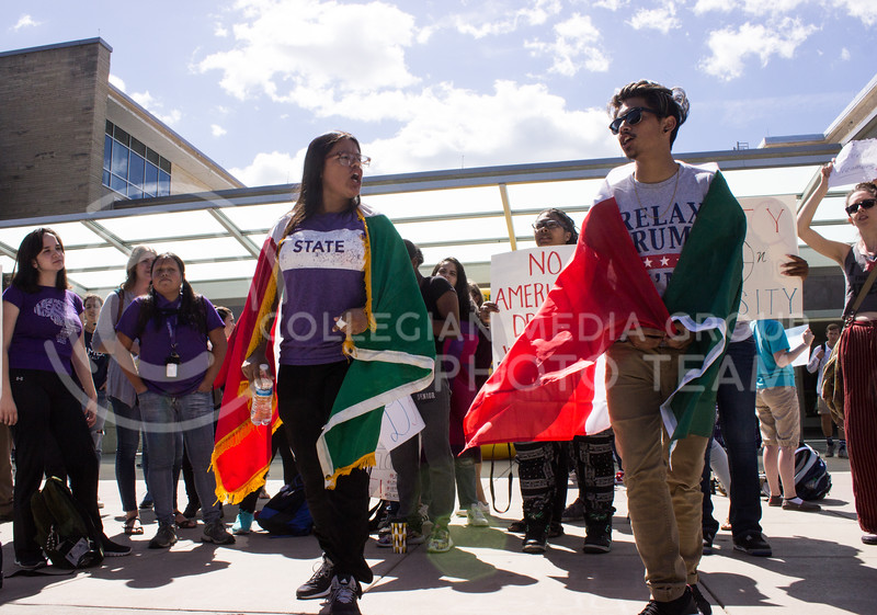 Leslie Ramirez, sophomore in secondary education, and Alexavier Galicia, sophomore in mechanical engineering, lead a chant together at a rally for Deferred Action for Childhood Arrival (DACA) recipients. The rally was held in Bosco Plaza on September 6, 2017, days after President Trump announced efforts would be made to roll back DACA. (Regan Tokos | Collegian Media Group)