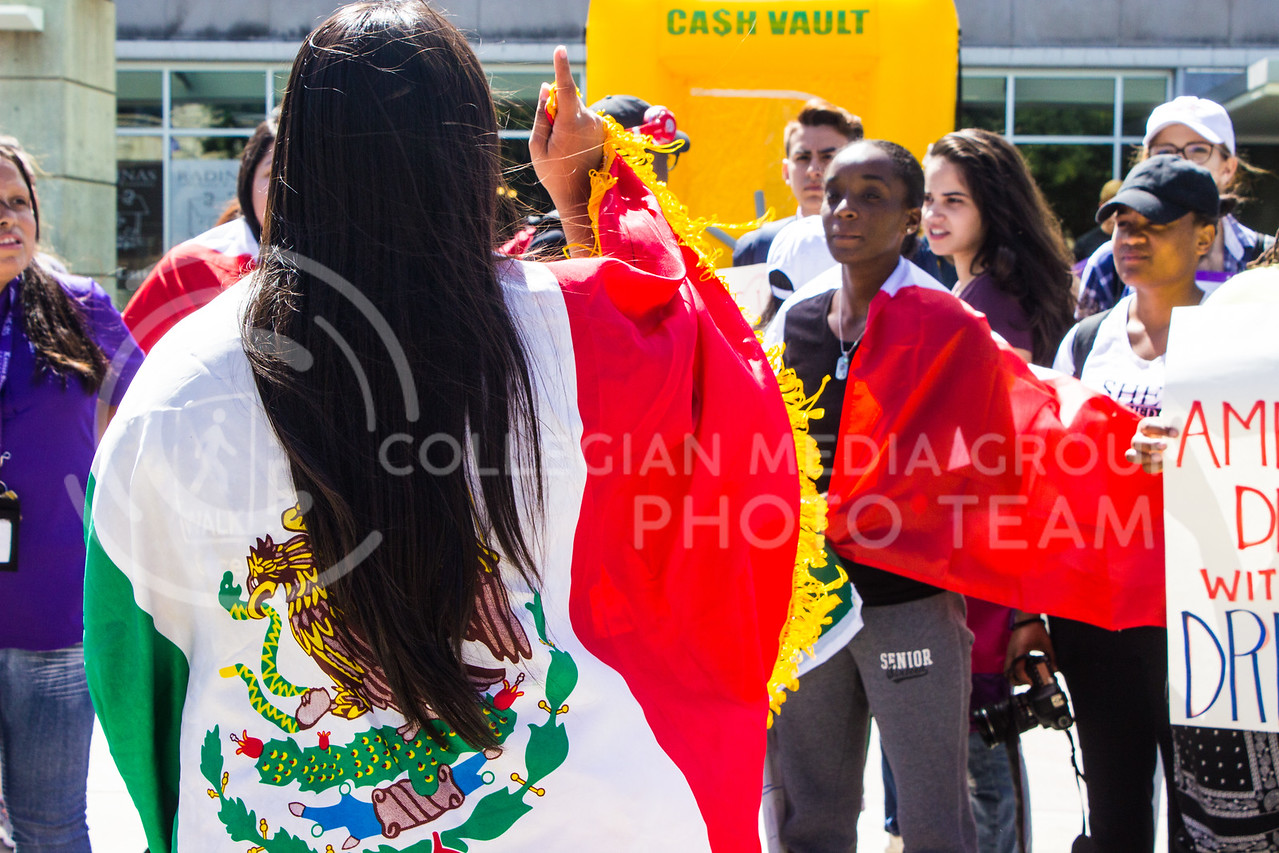 Leslie Ramirez, sophomore in secondary education, wears a Mexican flag over her shoulders with pride at a rally in support for Deferred Action for Childhood Arrival (DACA) recipients. A rally was held in Bosco Plaza on September 6, 2017, days after President Trump announced efforts would be made to roll back DACA. (Regan Tokos | Collegian Media Group)