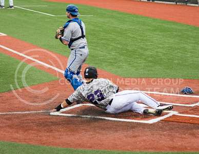 Senior 1st baseman Jake Scudder slides into home plate at the K-State baseball game against Eastern Illisnois University at Tointon Family Stadium on Mar. 5, 2017. (John Benfer | The Collegian)